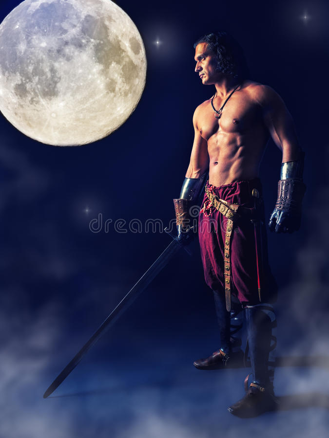 Half naked warrior with a sword in the mystic background stock image