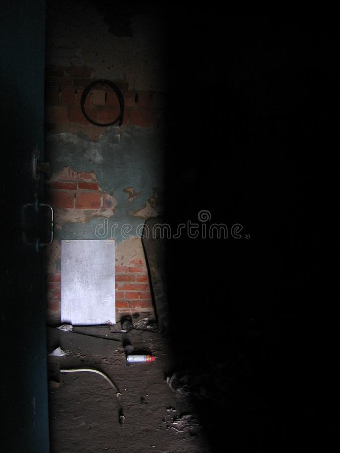 A half-open door to an abandoned room on a dirty floor lighting penetrates royalty free stock image