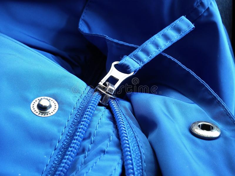 Half-open sewing lock on a blue synthetic fabric jacket. Open sewing buttons royalty free stock photography