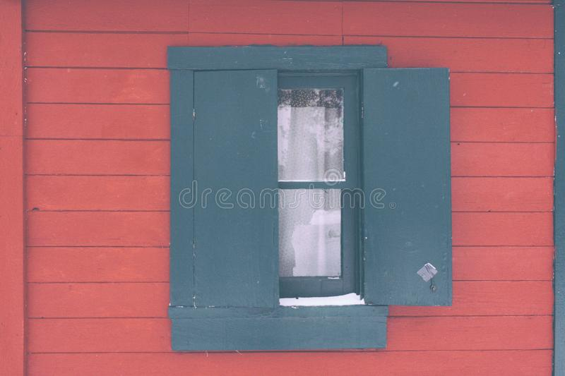 Half-opened blue window on a red wooden background stock photos