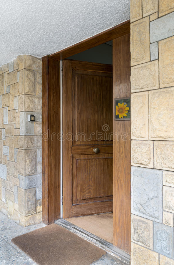 Half opened front wooden door at a stone bricks wall. Half opened front wooden door at a stone bricks colored wall and a brown doormat royalty free stock image