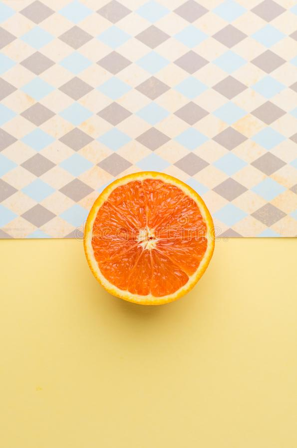Half Orange on Geometry Yellow Pastel Background. Creative Concept. Half Orange on Geometry Yellow Pastel Background, Top View stock photo