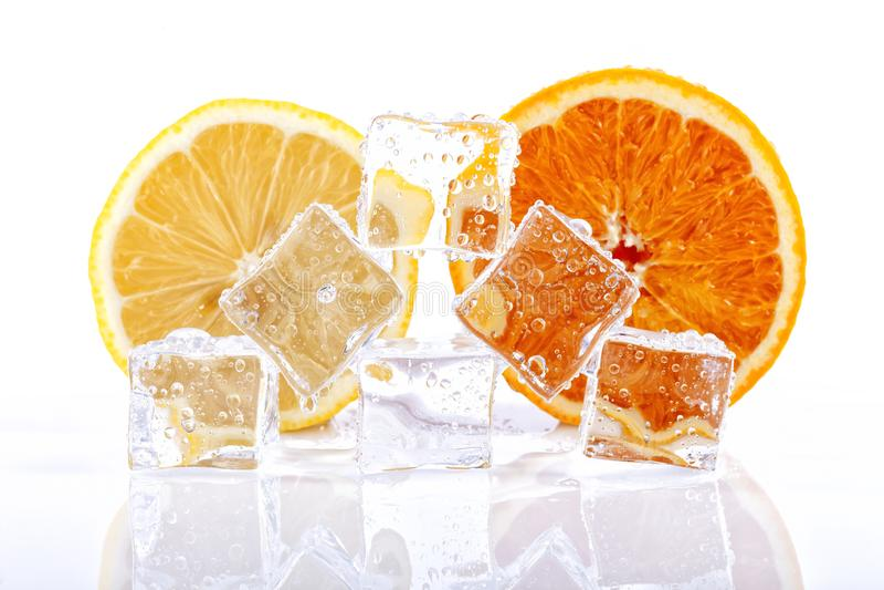 Half orange and half a lemon behind some ice cubes melting isolated royalty free stock photo