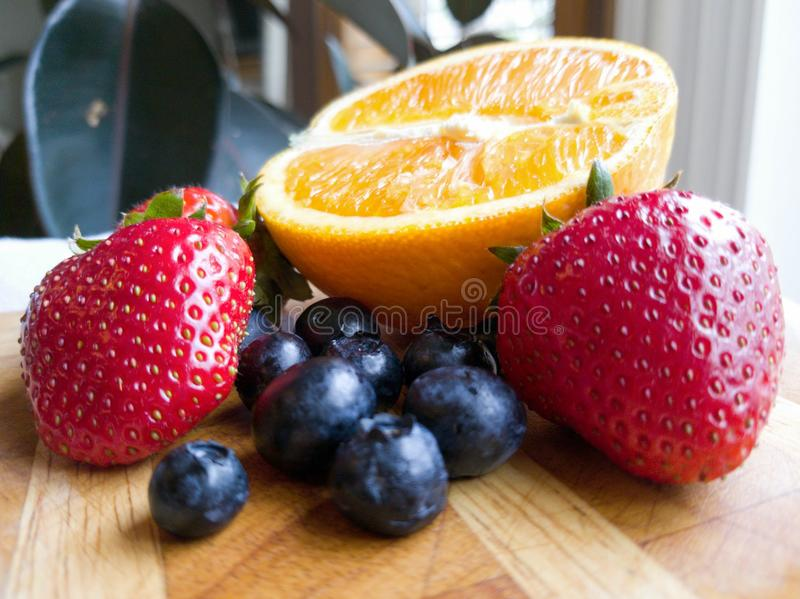Orange Strawberry Blueberry Fruits on Wooden Cutting Board royalty free stock images
