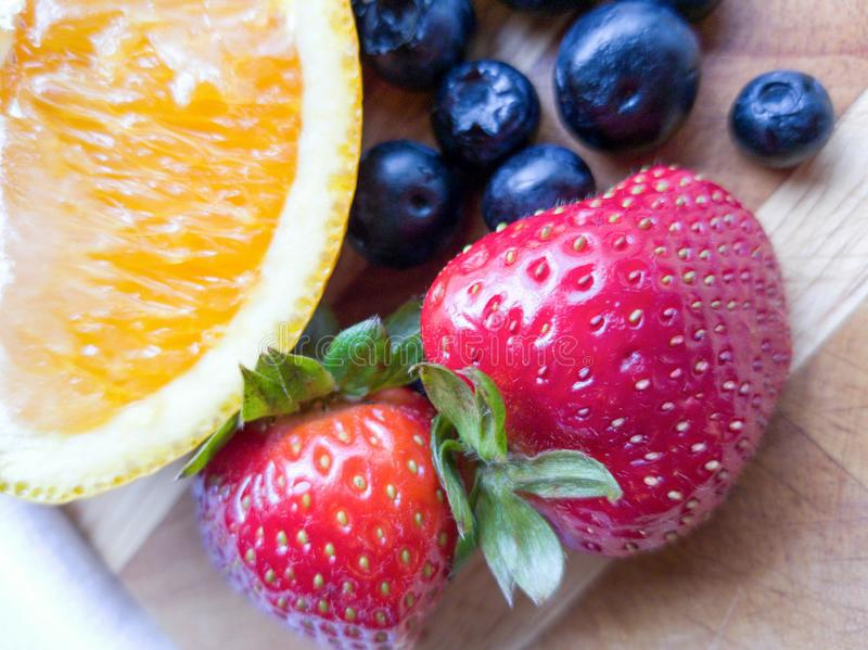 Orange Strawberry Blueberry Fruits on Wooden Cutting Board royalty free stock photos