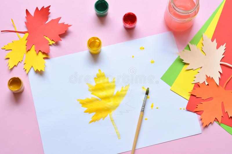 Half-painted maple leaf, paint and brush. Unfinished work. Quitter. Pass of difficulties. Autumn melancholy stock photography