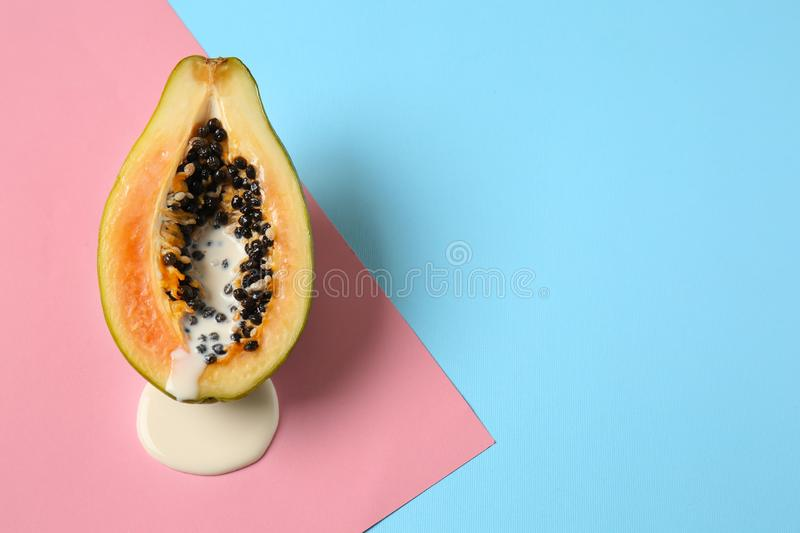 Half of papaya with dripping white liquid on color background. Erotic concept royalty free stock photo