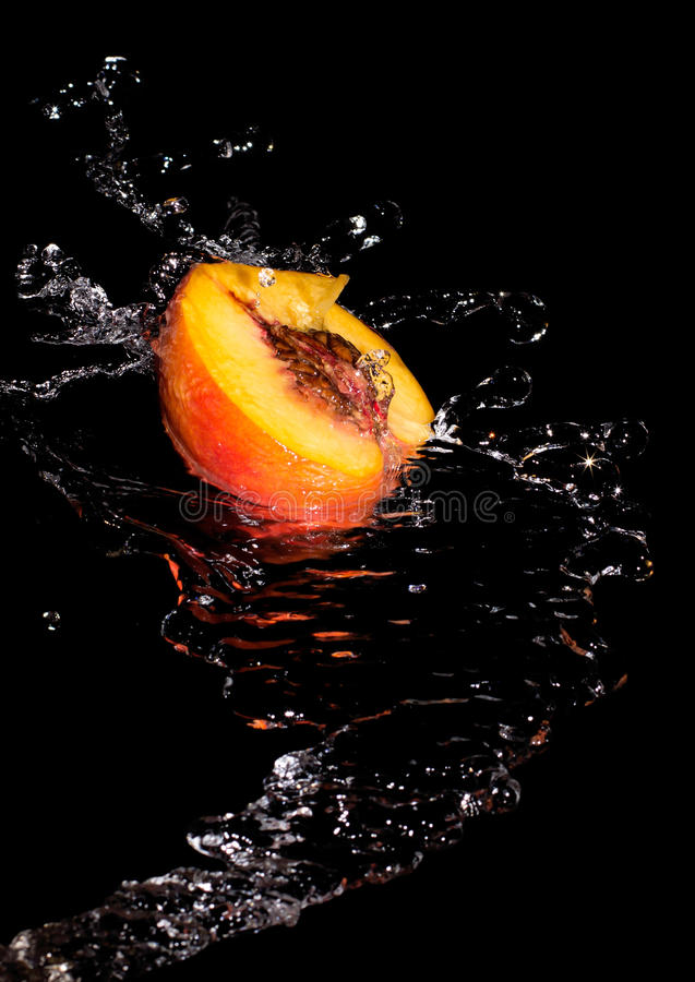 Half peach and water. Half a peach in a spray of clean transparent water on a black background royalty free stock photos