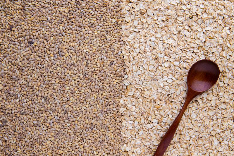 Half picture whole grain barley and half oatmeal cereal with wooden spoon, top view royalty free stock image