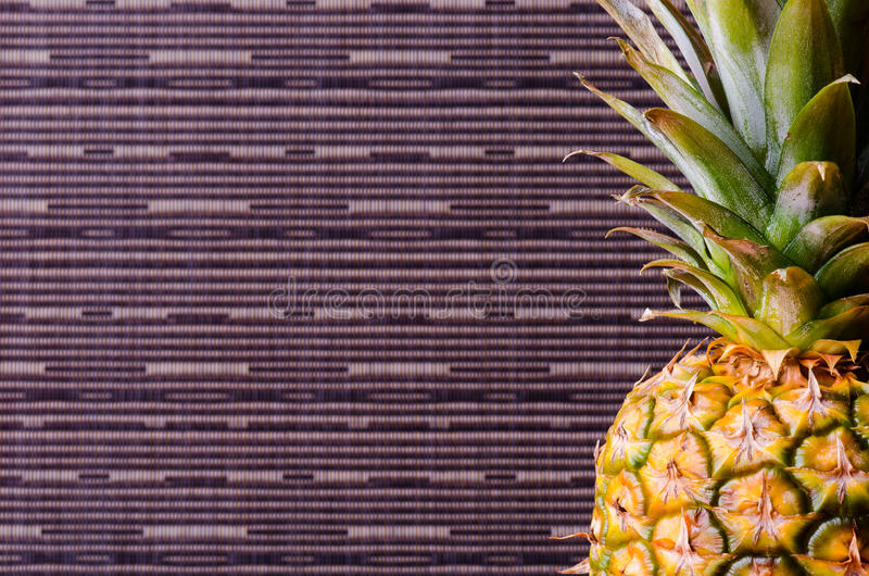 Half of pineapple in right side on gray stripes background, vertical shot. Picture presents half of pineapple in right side on gray stripes background, vertical stock photo