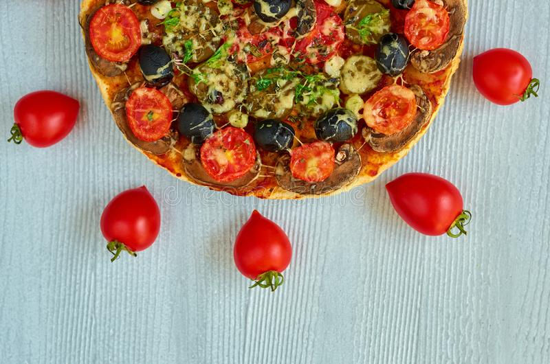 A half of pizza on the gray background with copy space. Vegetarian pizza with mushrooms, tomatoes, black olives and spices royalty free stock photo