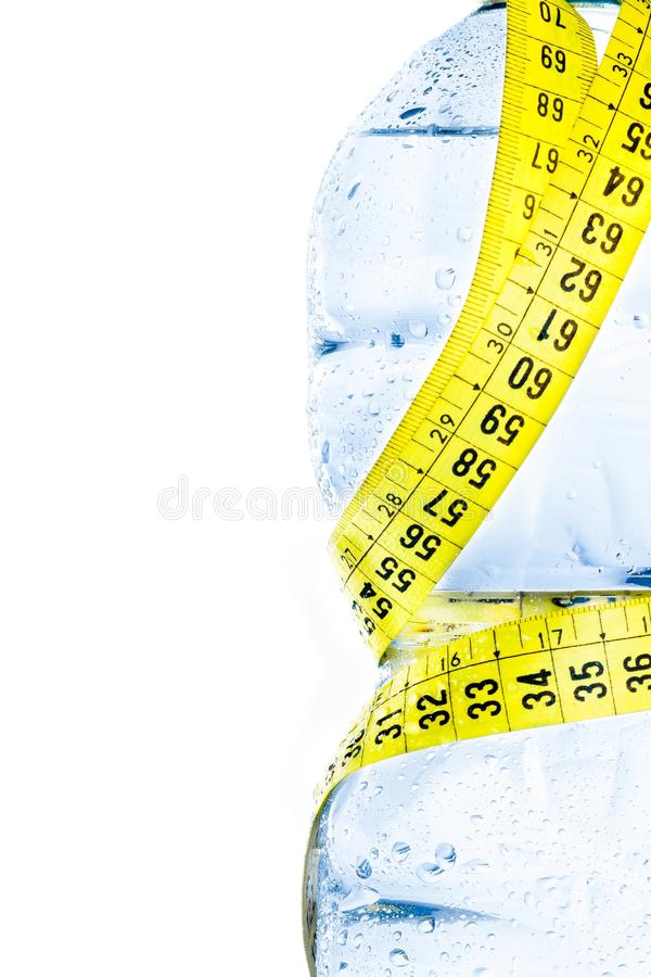 Half plastic bottle with water, drops and measuring tape, concept of nutrition and diet royalty free stock photo