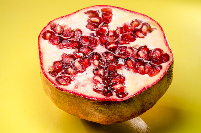Half of pomegranate on yellow background, horizontal shot stock image