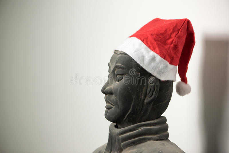 Half profile of Chinese terracotta warrior stature wearing santa hat. Face, isolated on white background stock photos