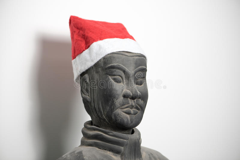 Half profile of Chinese terracotta warrior stature wearing santa hat. Face, isolated on white background stock images