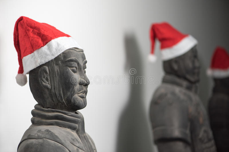 Half profile of Chinese terracotta warrior stature wearing santa hat. Upper body, with more statues in the background, selective focus stock image