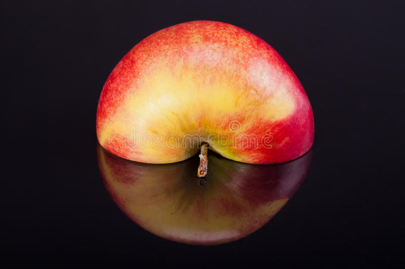Half of red apple with reflection isolated on black background stock photo