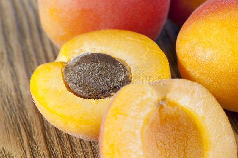 Half ripe apricot. A bunch of apricots lying on an old wooden table. one apricot is divided by a knife into two halves, in the one of which is a dark bone stock photo