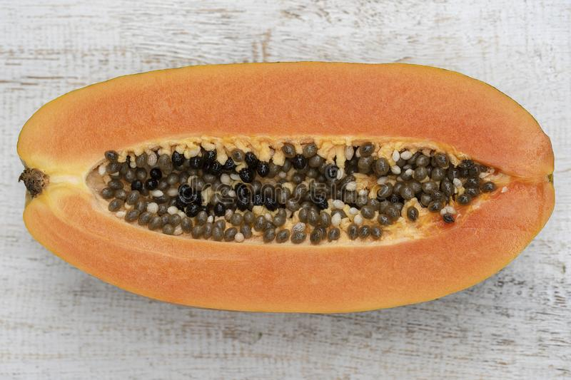 Slices of sweet papaya on white wooden background, close up. Half of ripe sweet papaya fruit with seeds on white wooden background, close up stock images