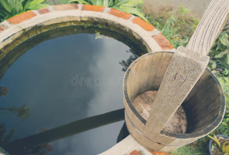 Half round brick water well with wooden bucket. On top royalty free stock photo