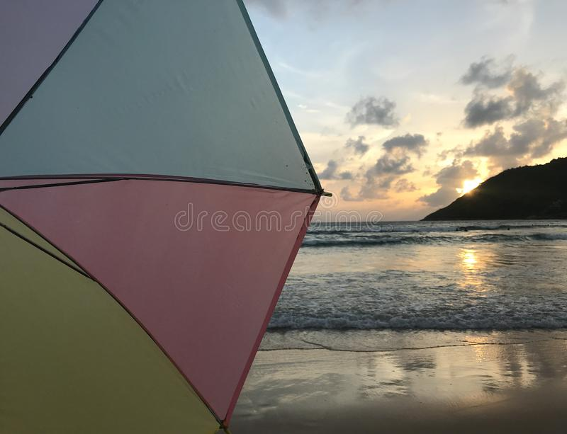 Half scene of sunset on beach with pastel colorful umbrella royalty free stock images