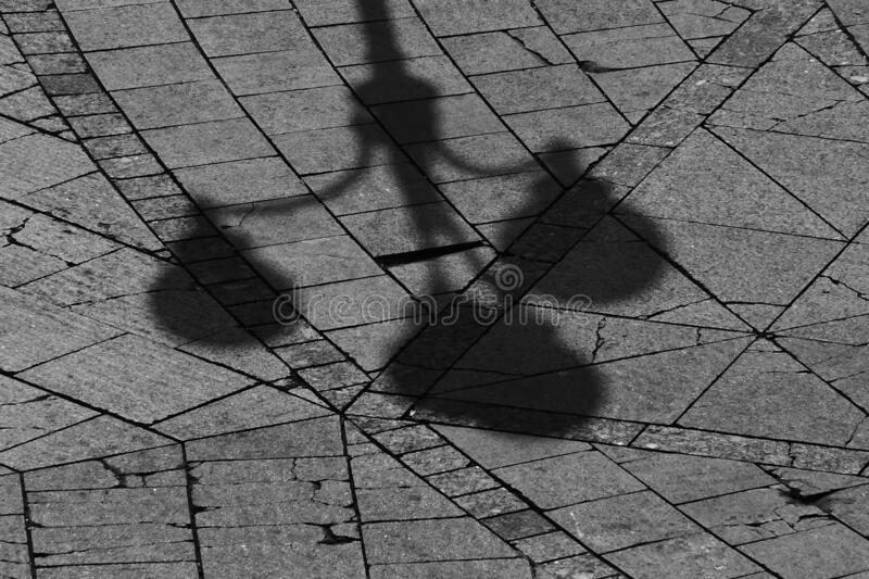 Half the shadow of a man and the legs of the oldest man with a cane. Half the shadow of a man on a wide brick pavement and the legs of the oldest man in royalty free stock photo