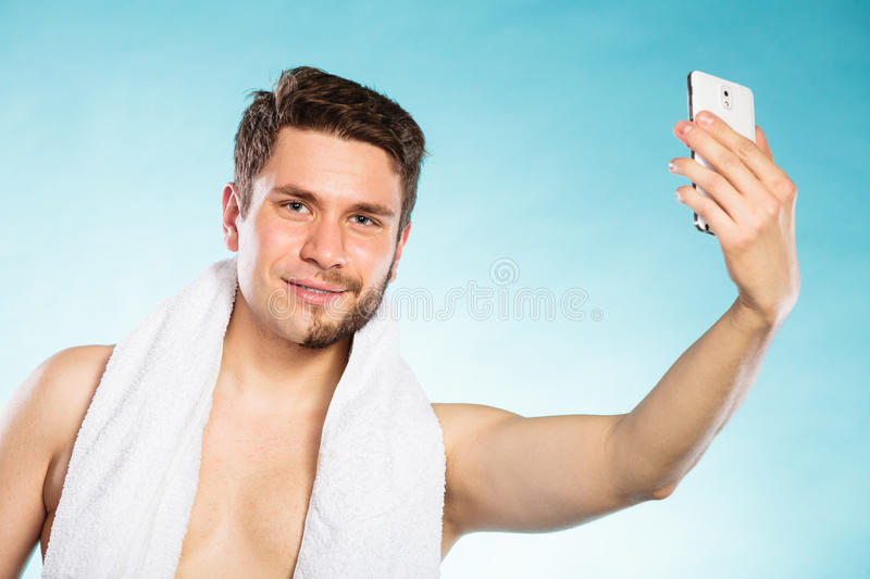 Half shaved man taking selfie self photo. Young man with half shaved face beard hair taking selfie self photo with smartphone camera. Handsome guy on blue. Skin stock photos