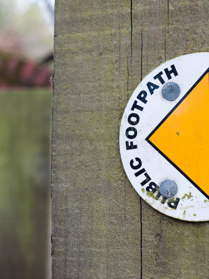 Half of A Sign on A Wood Post Saying Public Footpath with Semi-Circle and Yellow Arrowhead Leading to the Left to the Pathway royalty free stock photography