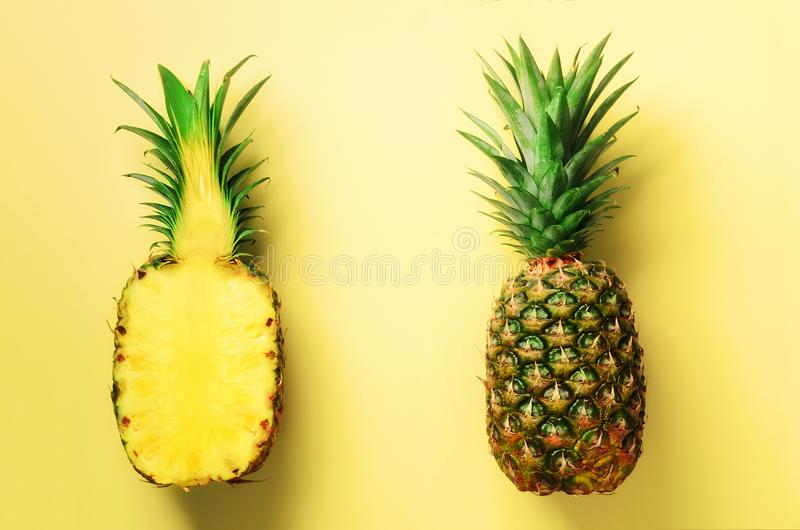 Half slice of fresh pineapple and whole fruit on yellow background. Top View. Copy Space. Bright pineapples pattern for royalty free stock images