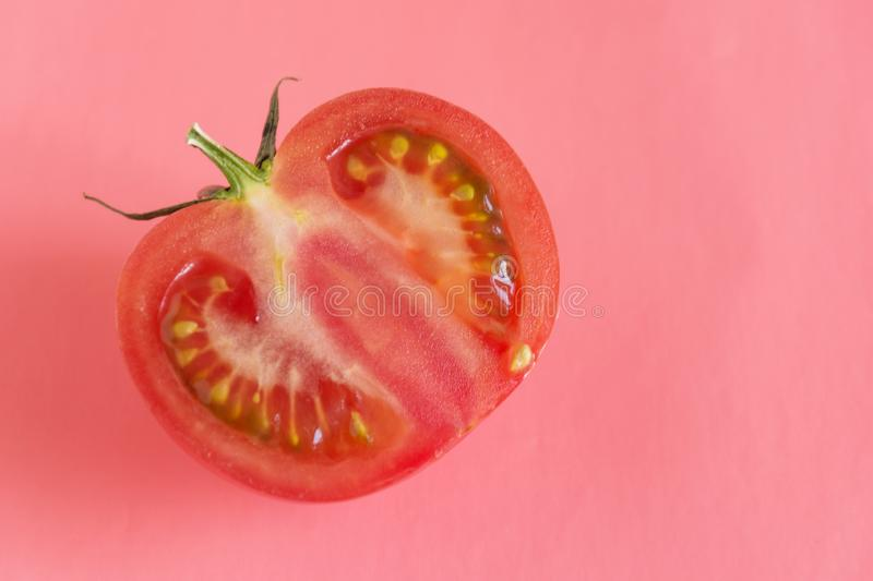 Half sliced tomato closeup on pink background stock photo