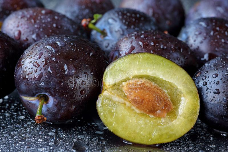 Half sliced and whole Damson plums with the stone on a black cutting board with water drops. Macro food background with fresh, org royalty free stock image