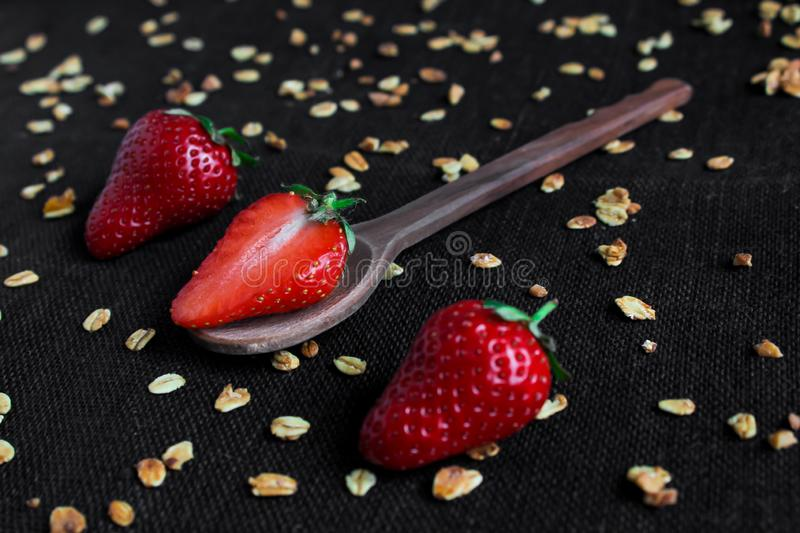 Half strawberry on a wooden spoon, near the whole berries and flakes on a black background royalty free stock photo