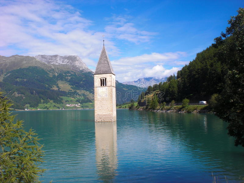 Half-submerged church bell tower. Half-submerged bell-tower of the church of St. Katharina in the village of Graun on the Reschen Lake, Reschen Pass royalty free stock photo