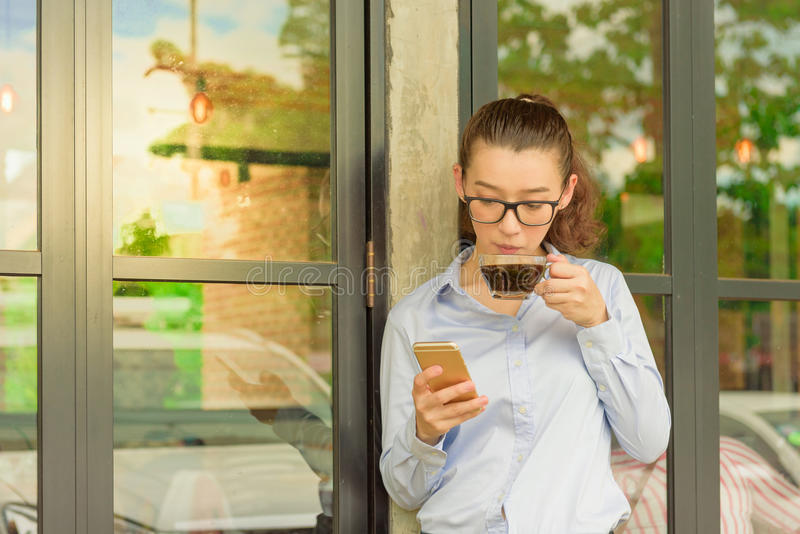 Half Thai half American hold iphone in right hand and glass of h. Ot black coffee in left hand standing against glass door at coffee shop,freelance woman stock images