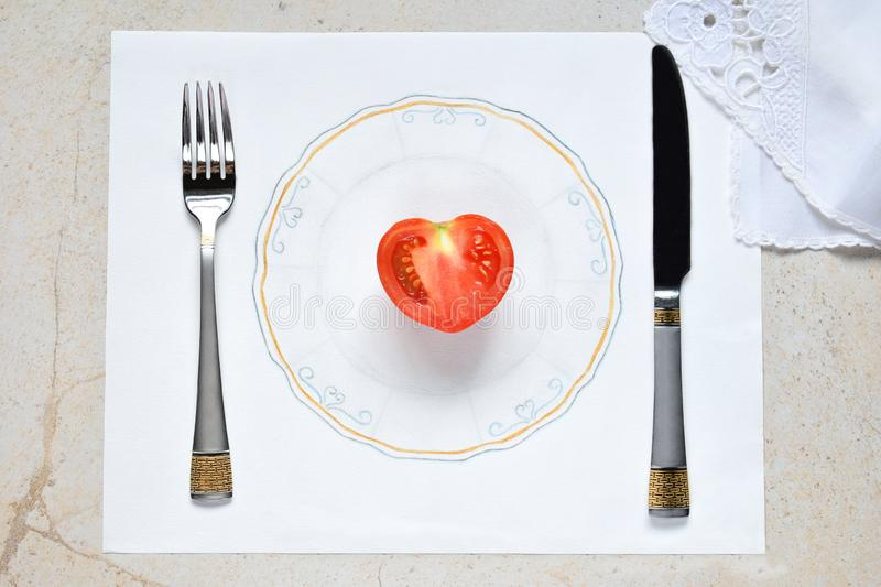 Half a tomato in the form of a heart on a painted plate. Concept of vegetarian food. Restrictions on food. Small portion of food o. N big plate stock images