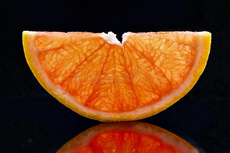 Half transparent slice of grapefruit on a black background. royalty free stock photos