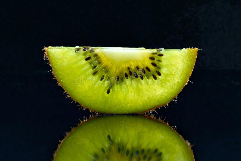 Half transparent slice of kiwi on a black background. royalty free stock photo