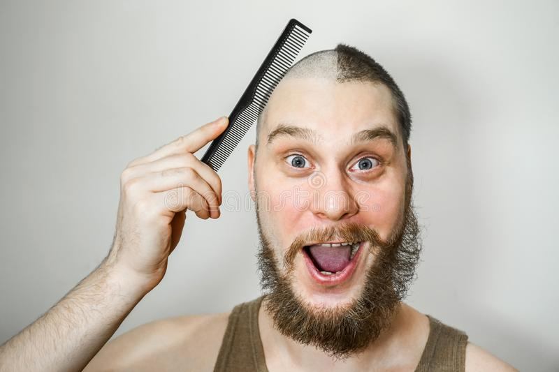 Half trimmed bald guy on isolated background. man hold comb and clipper. Concept of hair loss, alopecia, transplantation. Half trimmed bald guy on isolated stock photo