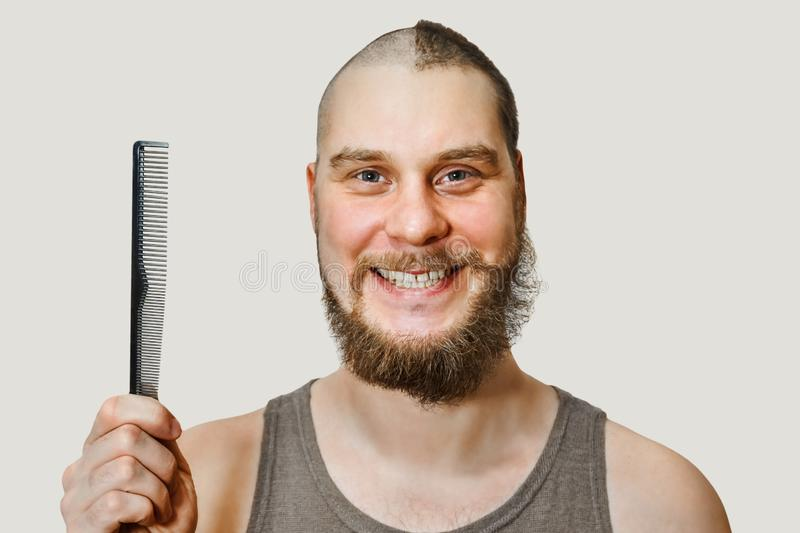 Half trimmed bald guy on isolated background. man hold comb and clipper. Concept of hair loss, alopecia, transplantation. Half trimmed bald guy on isolated royalty free stock image