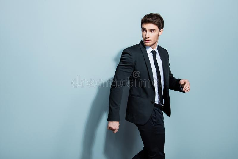 Half-turned portrait of handsome busy confident attractive serious minded thoughtful stunning entrepreneur going somewhere. Gesturing with hands looking to the royalty free stock photo