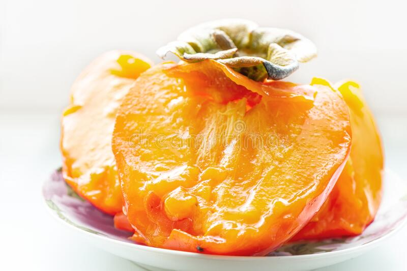 Half of a very ripe juicy orange persimmon is on the plate. Close up.  stock image