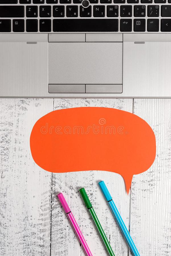 Half view trendy open laptop blank speech bubble facing downwards pens lying vintage wooden table. Personal computer royalty free stock image