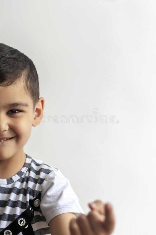Half view of 6 years old cute boy`s face. Little boy calling someone with his forefinger. Free space royalty free stock photo