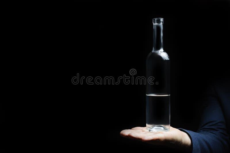 Half volledig is een lege fles wodka op een zwarte achtergrond stock foto