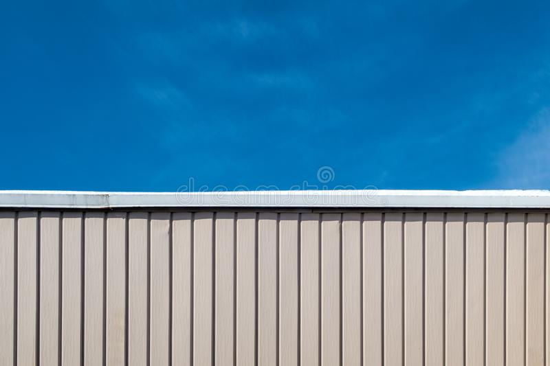 Half wall half blue sky. Top part of the picture is blue sky, bottom part is pink wall with patern lines royalty free stock photography