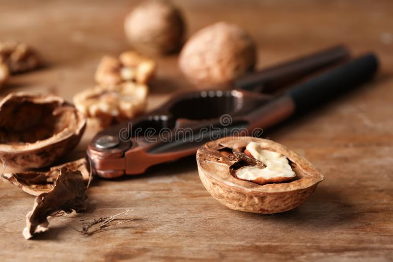 Half of walnut with shell and nutcracker on wooden table stock photos