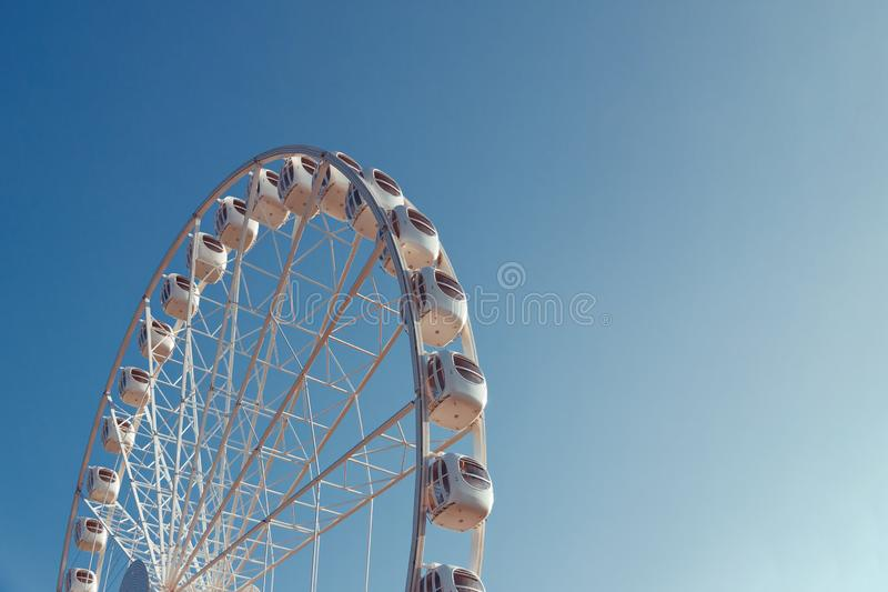 White metal ferris wheel with booths with windows against a blue sky, bottom view. Half of white metal review wheel with booths with windows against blue sky royalty free stock photo