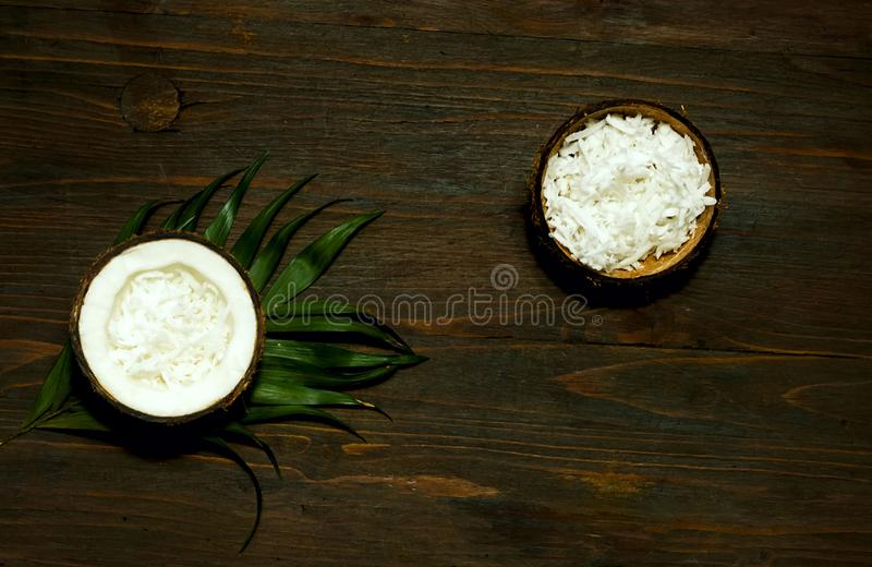 Half and whole coconuts. Coconut pattern on wooden background. Copy space, stock photography