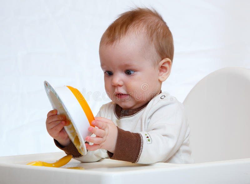 Half year old boy examines plate with puree. Isolated royalty free stock images