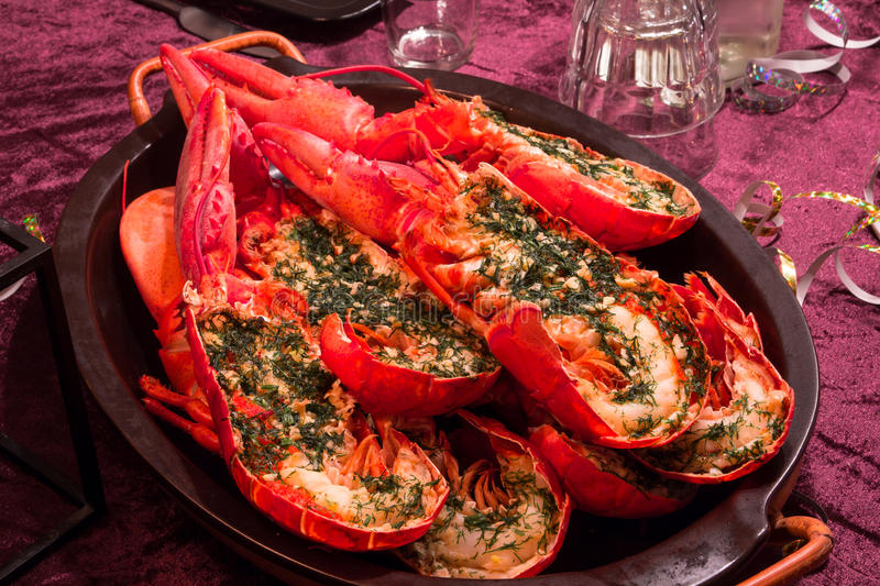 Halfed maine lobsters on a plate. Dish with cooked and halfed lobsters stock image